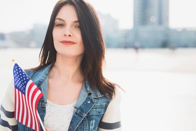 Femme tenant le drapeau américain en célébrant le 4 juillet à l'extérieur
