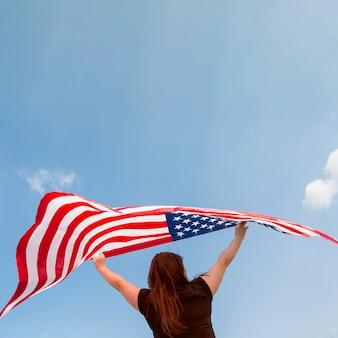 Femme tenant un drapeau américain