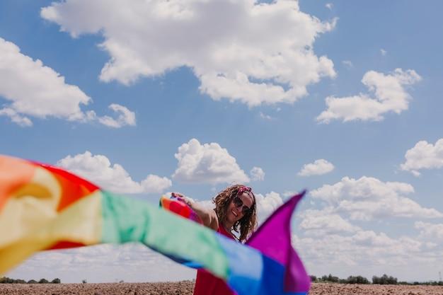 Femme tenant le drapeau arc-en-ciel gay sur ciel bleu et nuageux à l'extérieur. concept de bonheur, de liberté et d'amour pour les couples de même sexe. style de vie en extérieur