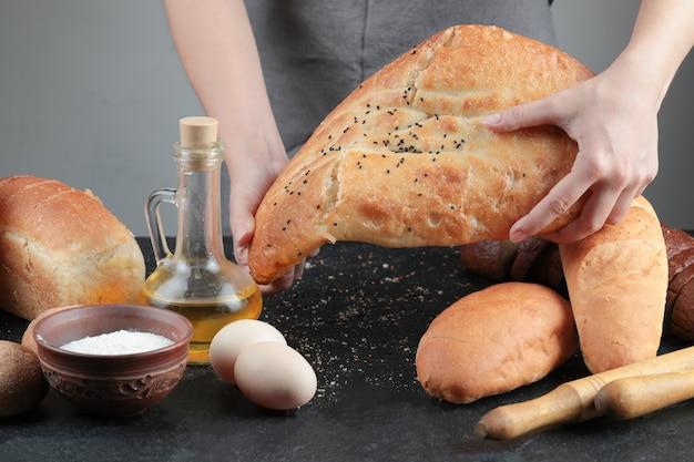 Femme tenant du pain sur une table sombre avec des œufs, un bol de farine et un verre d'huile.