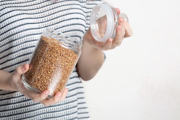 Femme tenant du sarrasin dans un bocal en verre pour le stockage. espace libre