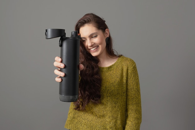 Femme tenant éco bouteille d'eau thermo intelligente réutilisable avec rappel de boisson, concept de mode de vie sain