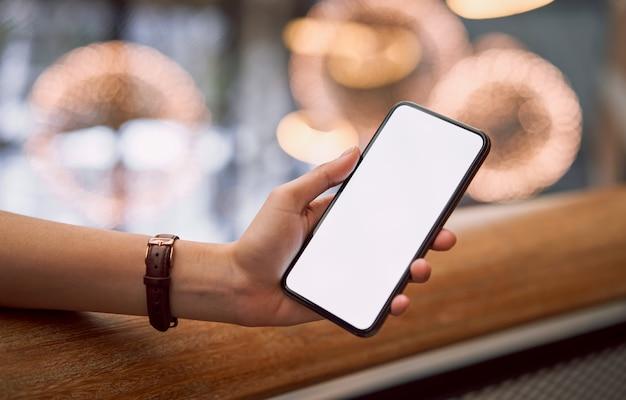 Femme tenant un écran vide smartphone dans le centre commercial. prenez votre écran pour mettre de la publicité.