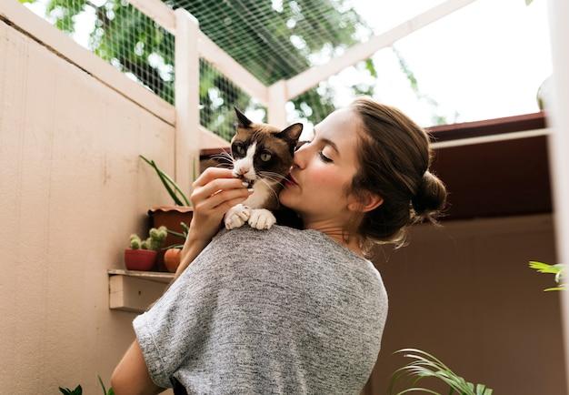 Femme tenant et embrassant son chat