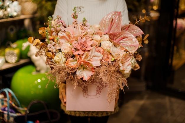 Femme tenant une énorme boîte de roses de couleur rose vif, succulettes et callas avec décor doré