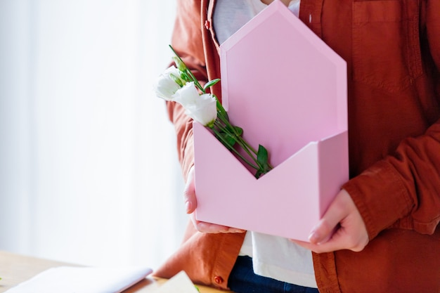 Femme tenant une enveloppe rose avec des roses blanches.