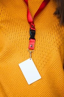 Femme tenant une étiquette de nom de badge, avec un espace vide maquette