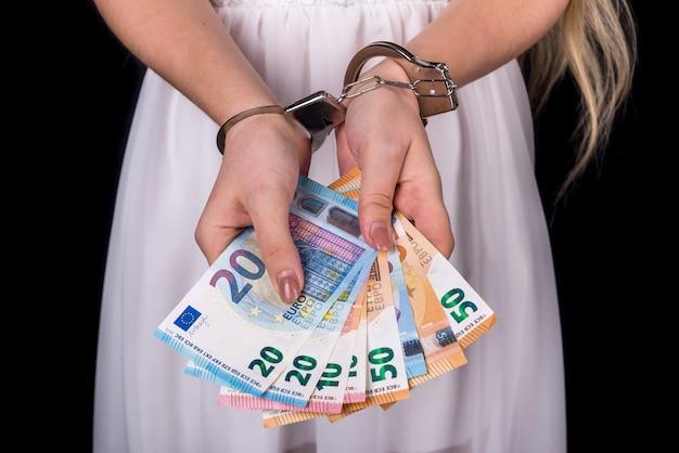 Femme tenant des euros d'argent dans des menottes