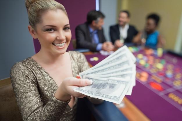 Femme tenant un fan de dollars