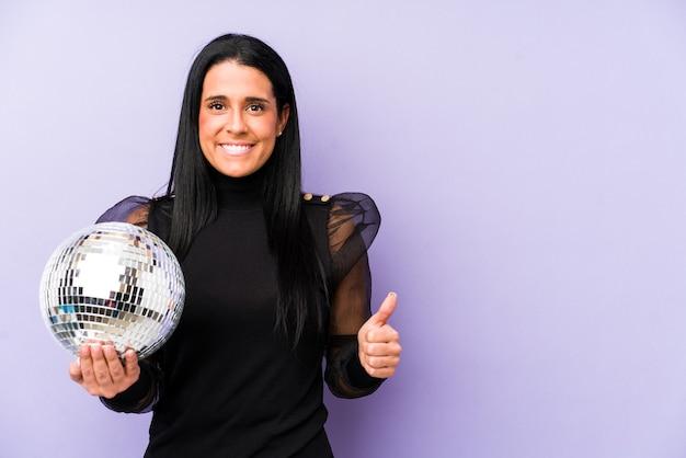 Femme tenant une fête de balle isolée sur mur violet souriant et levant le pouce vers le haut