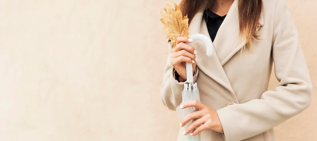 Femme tenant une feuille d'automne avec espace copie