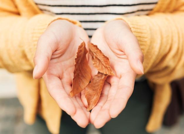 Femme tenant des feuilles d'automne gros plan