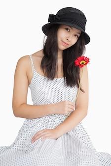 Femme tenant une fleur dans une robe à pois
