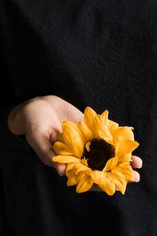 Femme tenant une fleur jaune vif à la main