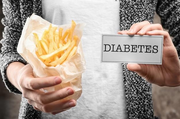 Femme tenant des frites et carte avec le mot «diabète», gros plan