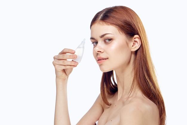 Femme tenant des gouttes pour les yeux dans ses mains un médicament pour la lumière de mode de vie de santé.