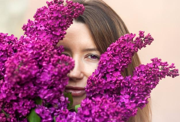 Femme tenant un grand bouquet de fleurs lilas bouchent