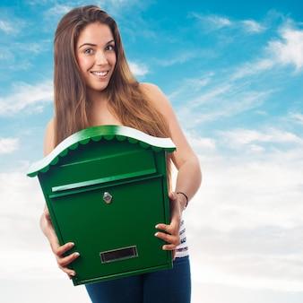 Femme tenant une grande boîte aux lettres verte
