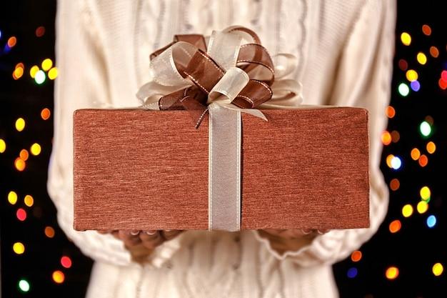 Femme tenant une grande boîte-cadeau décorée d'un bel arc, gros plan