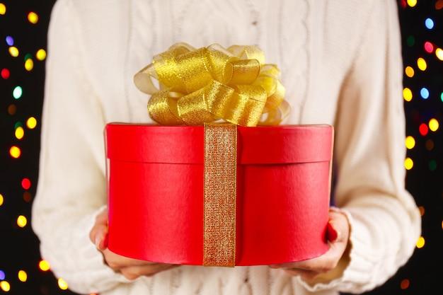 Femme tenant une grande boîte-cadeau rouge décorée d'un arc doré, gros plan