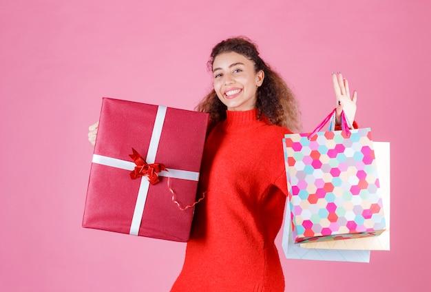 Femme tenant une grande boîte-cadeau rouge et plusieurs sacs à provisions colorés.