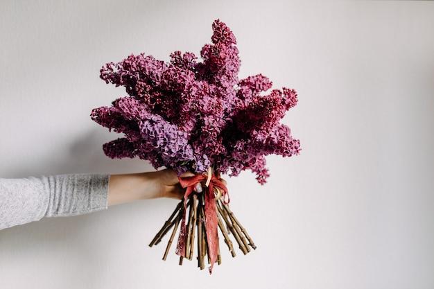 Femme tenant un gros bouquet de lilas violet sur fond de mur blanc
