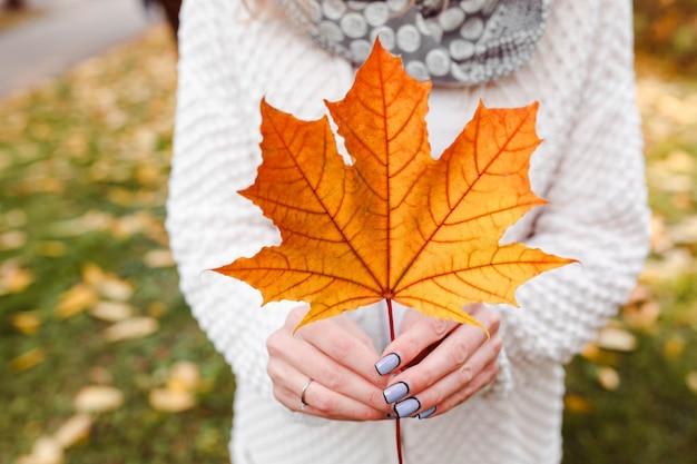 Femme tenant grosse feuille d'automne