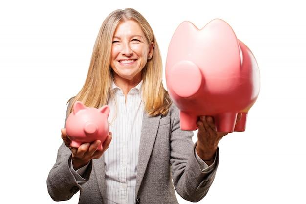 Femme tenant une grosse tirelire cochon et une petite tirelire