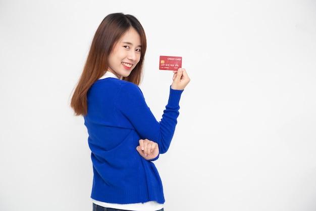 Femme tenant un guichet automatique ou une carte de débit ou de crédit isolée sur un mur blanc.
