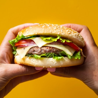 Femme tenant un hamburger à deux mains