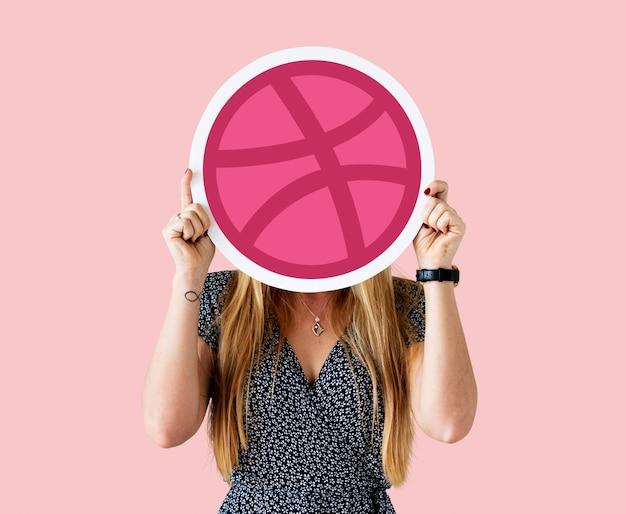 Femme tenant une icône de dribbble
