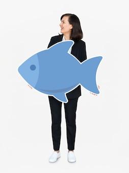 Femme tenant une icône de poisson bleu