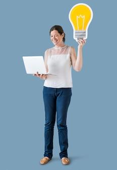 Une femme tenant des icônes d'ampoule