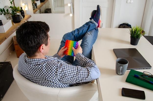 Femme tenant un jouet anti-stress à la main. rainbow square fidget toys pop-it. cliquez sur pop bubble.