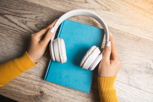 Femme tenant un livre audio sur la table
