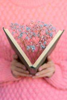 Femme tenant un livre ouvert avec un bouquet de fleurs séchées à l'intérieur
