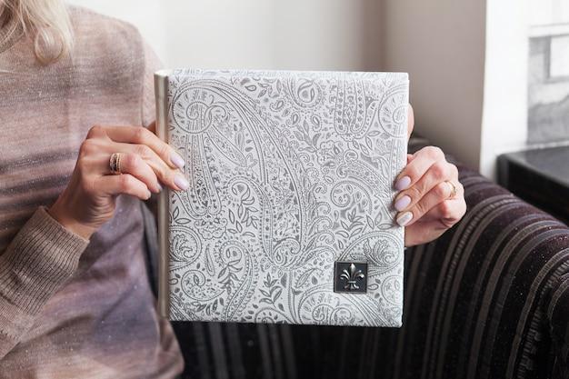 Femme tenant un livre photo de famille. album photo de mariage ou de famille avec revêtement en cuir véritable. couleur blanche avec estampage décoratif.