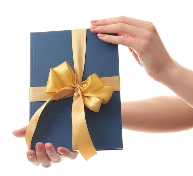 Femme tenant un livre avec un ruban comme cadeau sur blanc