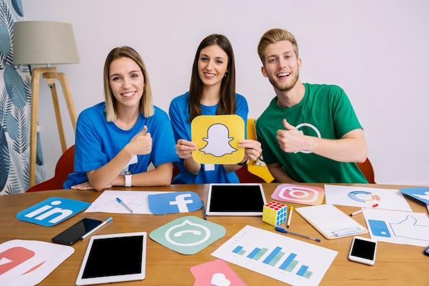 Femme tenant le logo youtube avec ses amis montrant signe thumbup