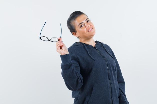 Femme tenant des lunettes à capuche et à la confiance. vue de face.