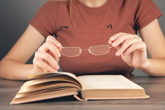 Femme tenant des lunettes devant un livre