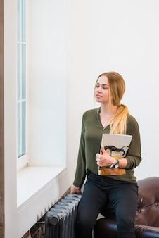 Femme tenant un magazine dans sa main en regardant la fenêtre