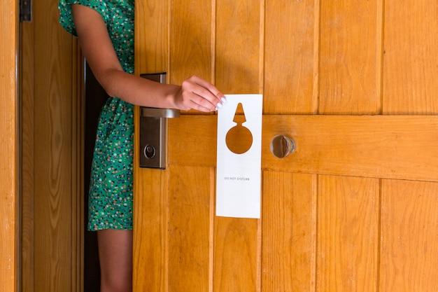 Femme tenant une main et accroche une enseigne ne pas déranger à la porte de l'hôtel