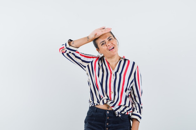 Femme tenant la main sur le front en chemise, jupe et à la délicieuse