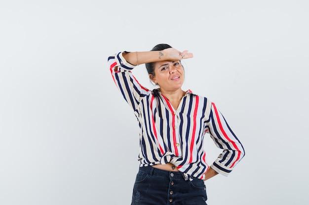 Femme tenant la main sur le front en chemise, jupe et à la recherche de mignon.
