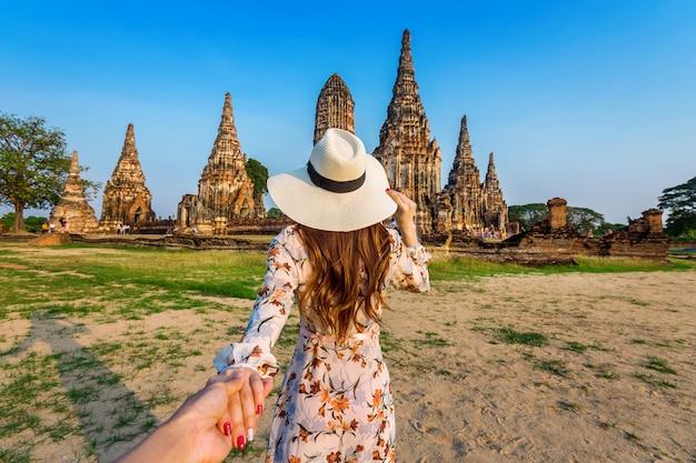 Femme tenant la main de l'homme et le menant au parc historique d'ayutthaya, temple bouddhiste wat chaiwatthanaram en thaïlande.