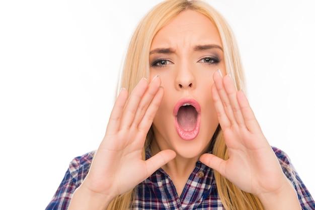 Femme tenant la main près de la bouche et crier