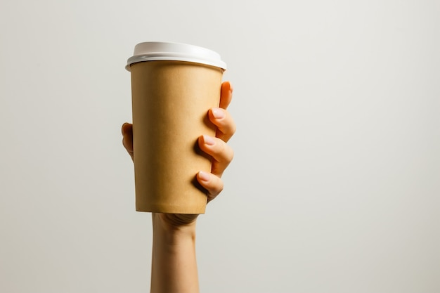 Femme tenant à la main une tasse de papier avec du café ou du thé. buvez l'heure du café. gobelet en papier jetable. belle jeune fille aux cheveux blonds. style décontracté, chemise blanche et jean. emporter. boisson chaude. espace vide