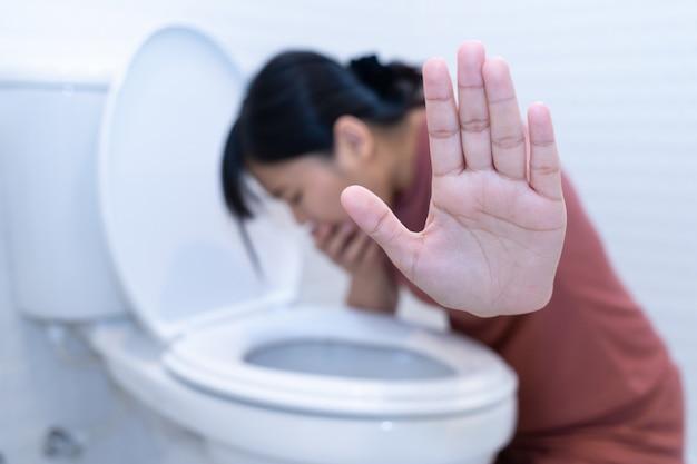 Femme tenant la main et vomissant dans les toilettes