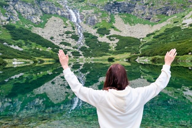 Femme tenant les mains au-dessus de la tête et saluant une vue imprenable sur la cascade